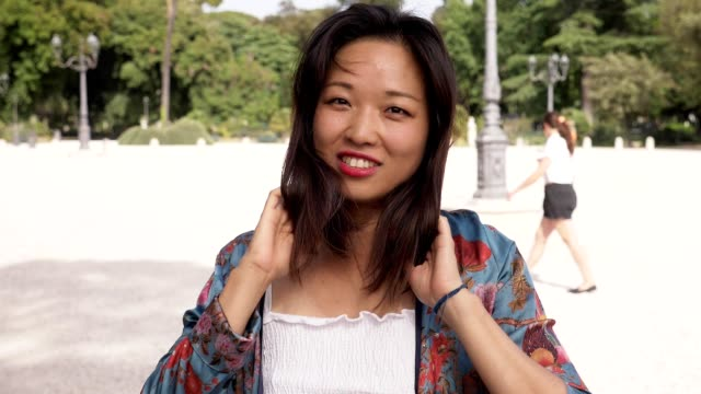 smiling attractive asian woman touching her hair looking at camera-slow motion - femminilità video stock e b–roll