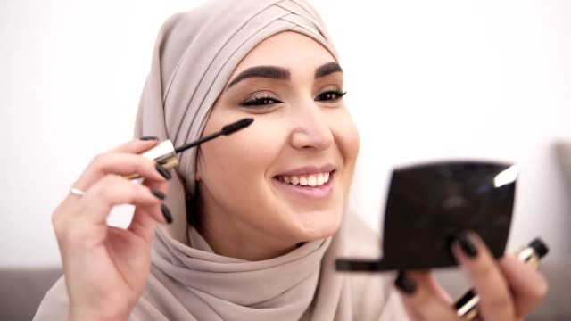 vídeos de stock e filmes b-roll de smiling, attractive muslim woman doing makeup professionally. brush eyelashes with mascara. wearing beige headscarf. white wall on the background. close up - rímel