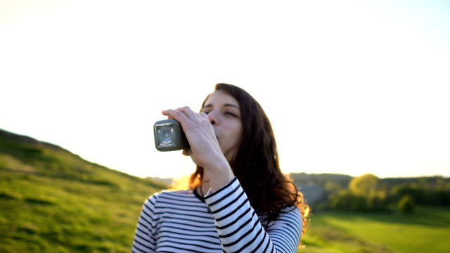 smiling attractive woman drinking healthy green vegetable smoothie in outdoor nature scenery during sunset - healthy green juice video stock e b–roll