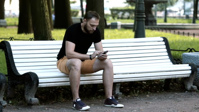 smiling attractive young man sitting on a bench in the park and using a smartphone video