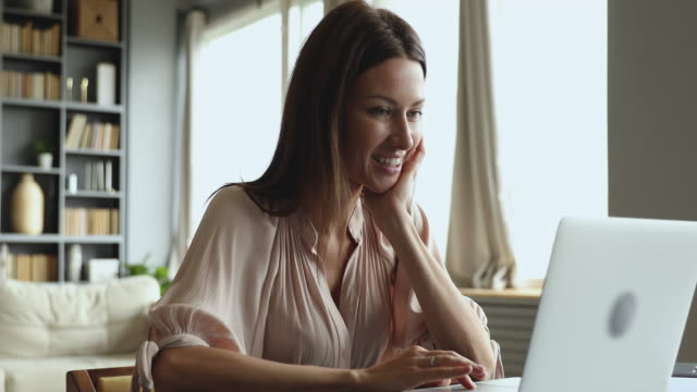 Smiling attractive young woman typing on laptop sit at table