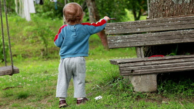 Smiling baby banging a wooden stick on the bench