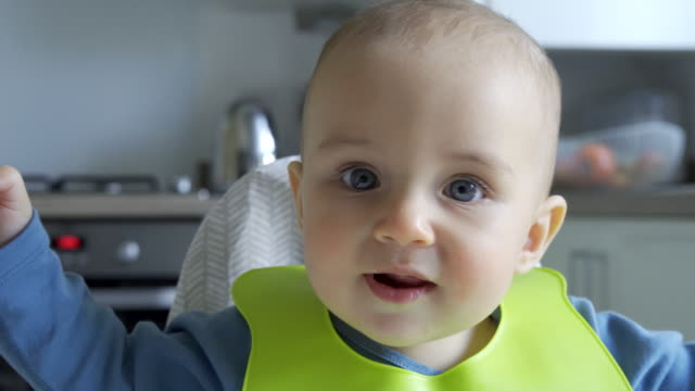 Smiling Baby Boy At Home In High Chair Being Fed Solid Food By Mother With Spoon