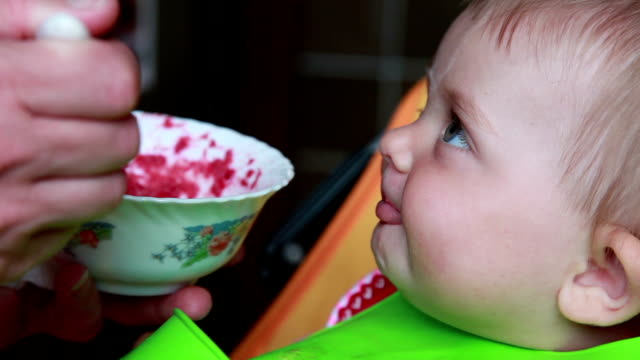 Smiling baby eating beetroot salad video
