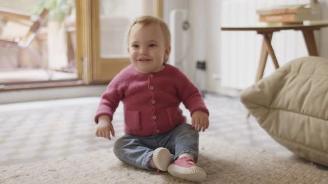 Smiling baby girl crawling on carpet at home Handheld shot of smiling baby girl crawling on carpet. Toddler is in baby clothing. She is enjoying at home. crawling stock videos & royalty-free footage