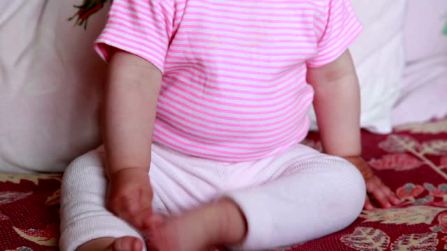 Smiling baby playing with her foot video
