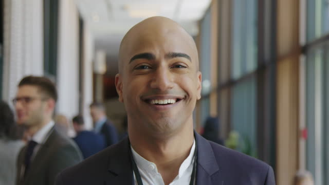 vídeos de stock e filmes b-roll de smiling bald businessman at seminar in hotel - funcionamento em rede