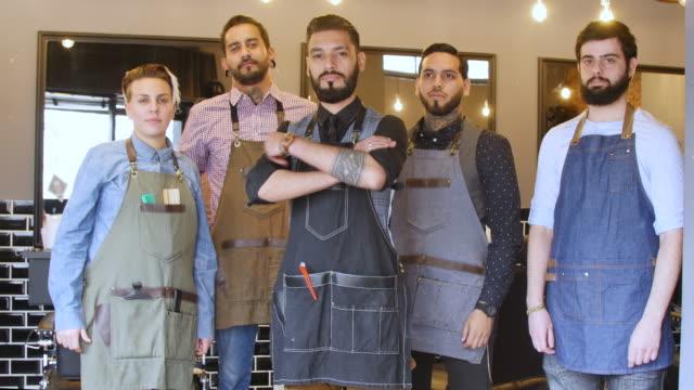 vidéos et rushes de souriant barbier debout bras croisés avec son équipe - coiffeur