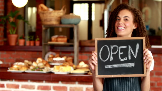 Smiling barista holding an open signboard video