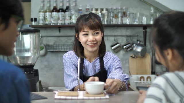 笑顔のバリスタがコーヒーを彼女の顧客に提供 - 飲食店点の映像素材/bロール