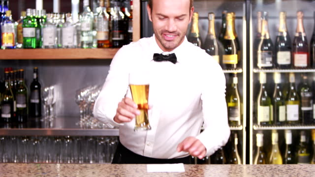 Sonriendo barkeeper sirve una cerveza - vídeo