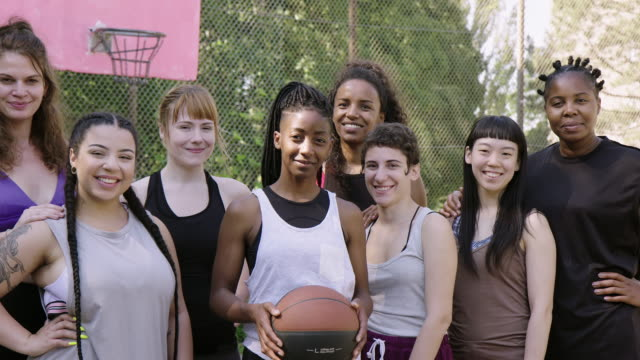 Smiling basketball team standing on sports court Portrait of smiling basketball players on outdoor court. Confident female athletes are standing together. They are in sportswear. plus size model stock videos & royalty-free footage