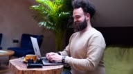 istock Smiling bearded hipster working from a cafe 1153507578