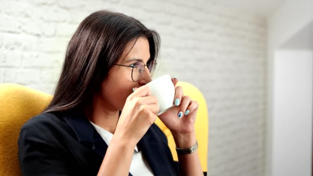 Smiling beautiful informal business woman relaxing drinking coffee at white room background