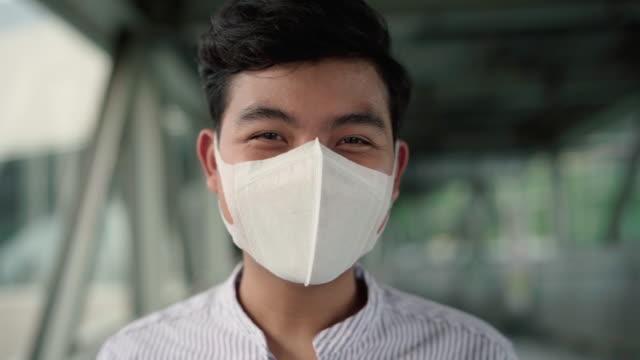 마스크 뒤에서 미소 짓고 있는 모습 - 잘생김 스톡 비디오 및 b-롤 화면