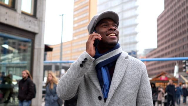 Smiling black businessman talking on a city street