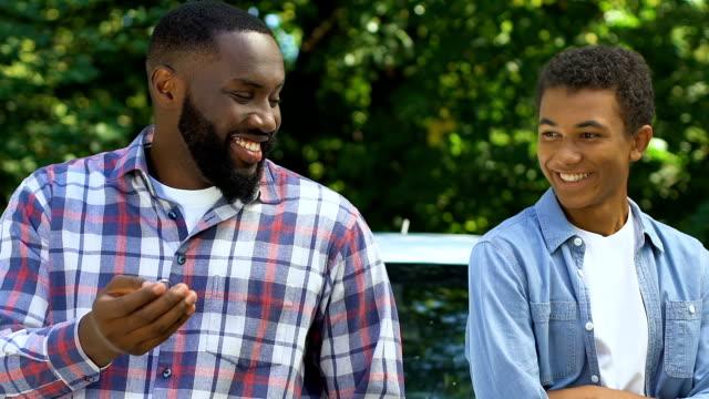 Smiling black dad throwing car keys to teenage son, both getting in vehicle