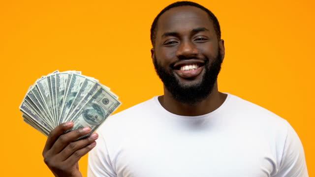 vídeos y material grabado en eventos de stock de sonriente chico negro señalando billetes de dólar en la mano, el pago del gobierno - prosperidad