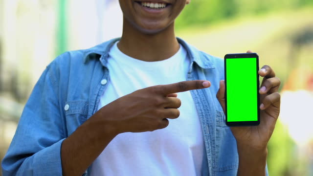 Smiling black male teenager pointing finger into smartphone with green screen