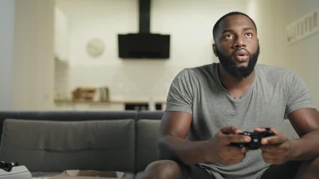 vídeos de stock e filmes b-roll de smiling black man playing video game at home kitchen. - man joystick