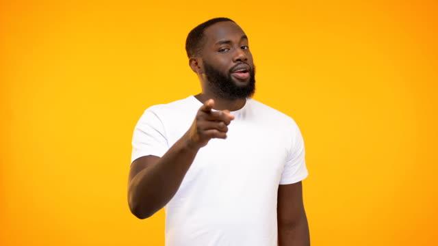 vídeos y material grabado en eventos de stock de sonriente hombre negro señalando el dedo, guiándose a sabiendas contra el fondo amarillo - prosperidad