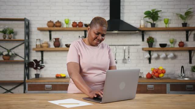 Smiling black obese lady types on laptop preparing for blog