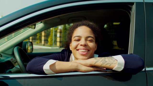 Smiling black woman looking out from car window Portrait of charming young african american woman in formalwear sitting in driver's seat, leaning on opened car window and looking with cheerful toothy smile while enjoying road trip in springtime. leaning stock videos & royalty-free footage