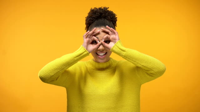 Smiling black woman making faces, having fun, isolated on yellow background video