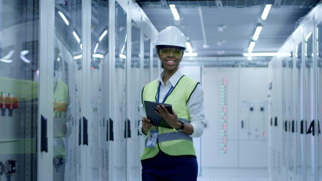 sorridente donna nera che lavora nel centro dell'impianto solare - componente elettrico video stock e b–roll