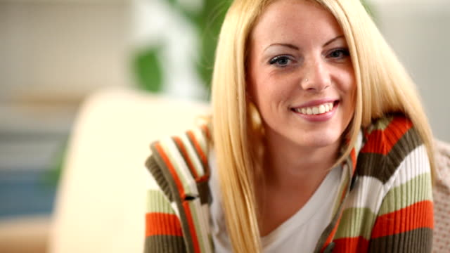 Smiling blond woman sitting on sofa. video
