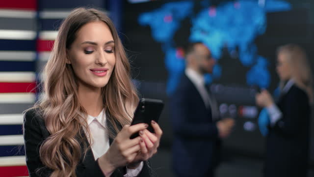 Smiling blonde business woman chatting use smartphone at hi tech innovation office workspace