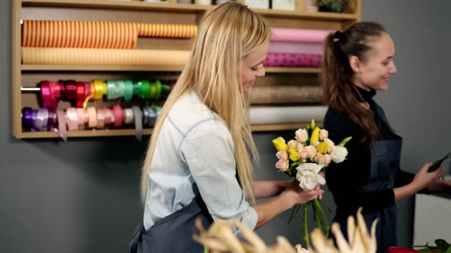 Smiling blonde florist in apron standing with her coworker at counter in floral shop while arranging bunch of flowers video