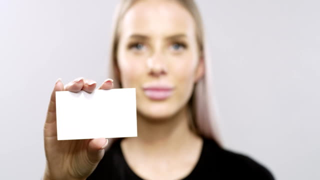 smiling blonde woman model holding a corporate card - video di credit card video stock e b–roll