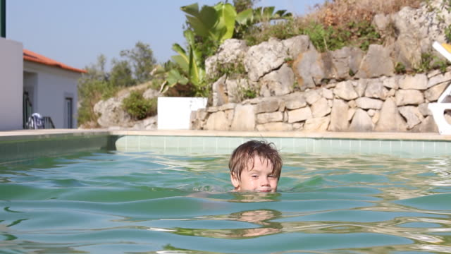 Smiling boy enjoying swimming pool video