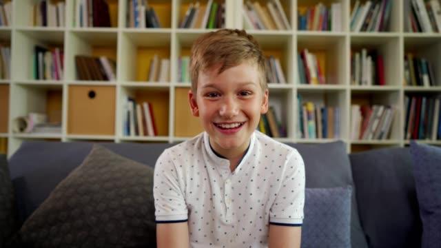 笑顔の少年は自宅でビデオ通話を持っています - 男の子点の映像素材/bロール