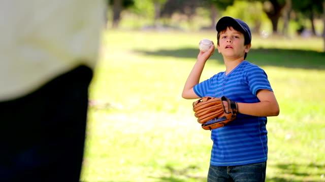 smiling boy playing baseball while standing upright - fånga bildbanksvideor och videomaterial från bakom kulisserna