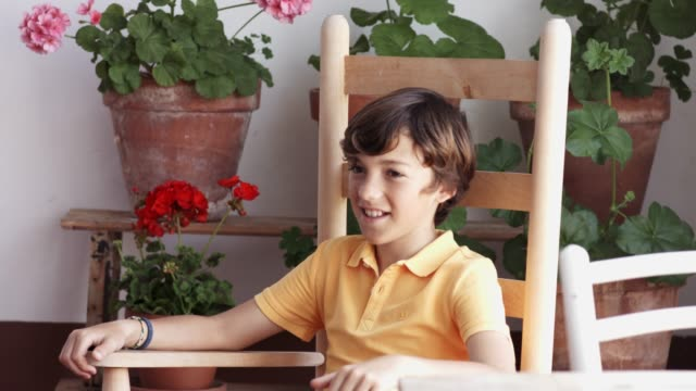 smiling boy resting on rocking chair against pots - fianco a fianco video stock e b–roll