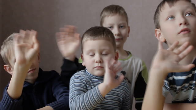smiling boys waving their hands and thumb up video