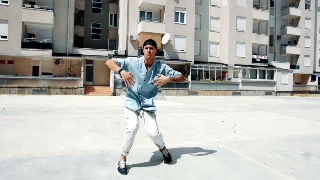 Smiling break dancer dancing in front of the building