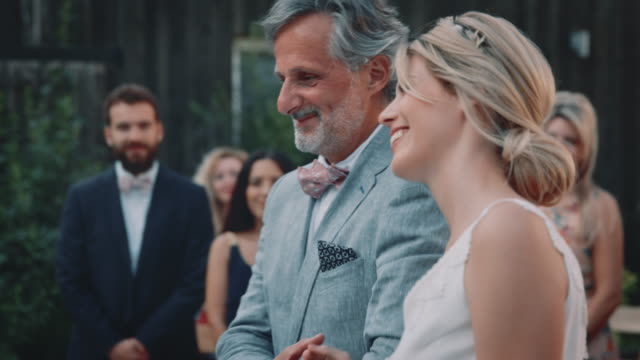 Smiling bride and father towards bridegroom