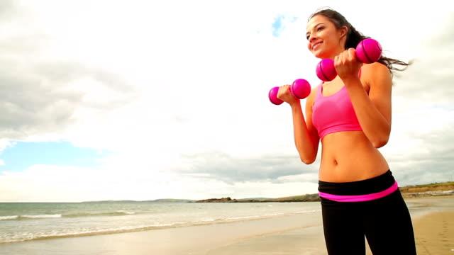 улыбка брюнетка поднимая гантели на пляже - спортивный бюстгальтер стоковые видео и кадры b-roll