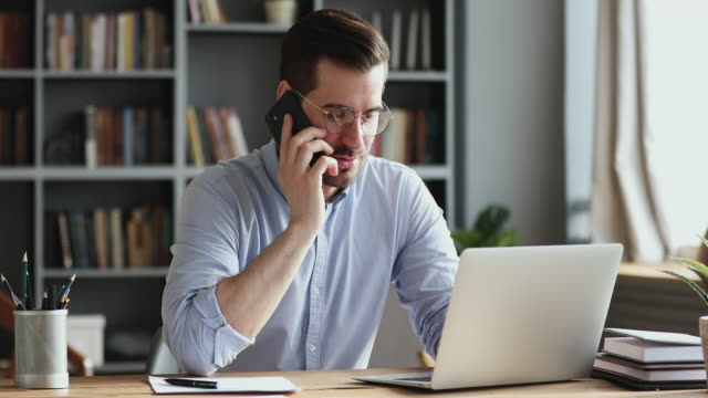 Smiling business man using laptop talking on phone in office