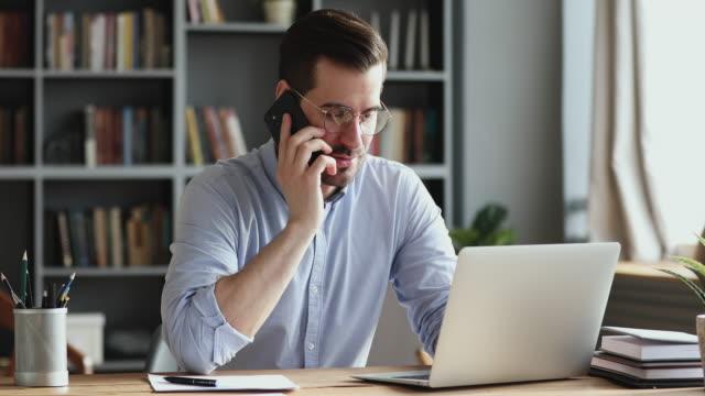 leende affärsman med hjälp av laptop talar i telefon på kontoret - använda telefon bildbanksvideor och videomaterial från bakom kulisserna