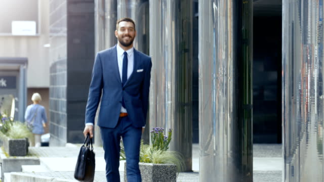 Smiling Business Man with a Bag Walks in a Business District. Weather Is Sunny He Looks Handsome in His Tailored Suit. video