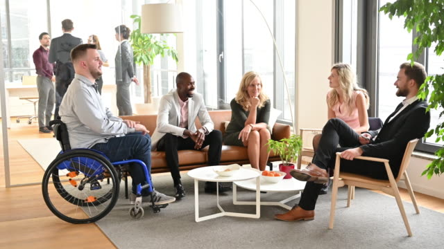Smiling business people relaxing and talking in office lobby Wide angle view of diverse group of male and female business executives sitting in modern office lobby and talking. disability stock videos & royalty-free footage
