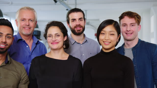 Smiling business team standing together in office
