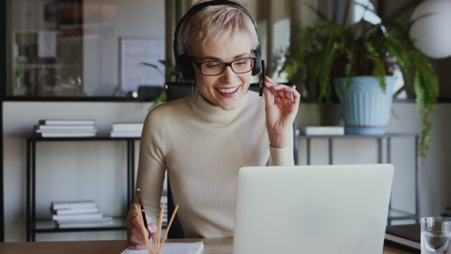 Smiling business woman wearing headset conference calling on laptop