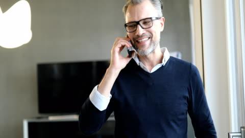 vídeos de stock e filmes b-roll de smiling businessman discussing on mobile phone - a usar um telefone