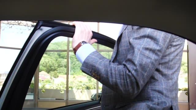 車に入るビジネスマンを笑顔と後部座席に座っています。 - 入る点の映像素材/bロール