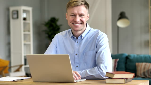 Smiling Businessman Looking at Camera while Working on Laptop Smiling Businessman Looking at Camera while Working on Laptop satisfaction stock videos & royalty-free footage